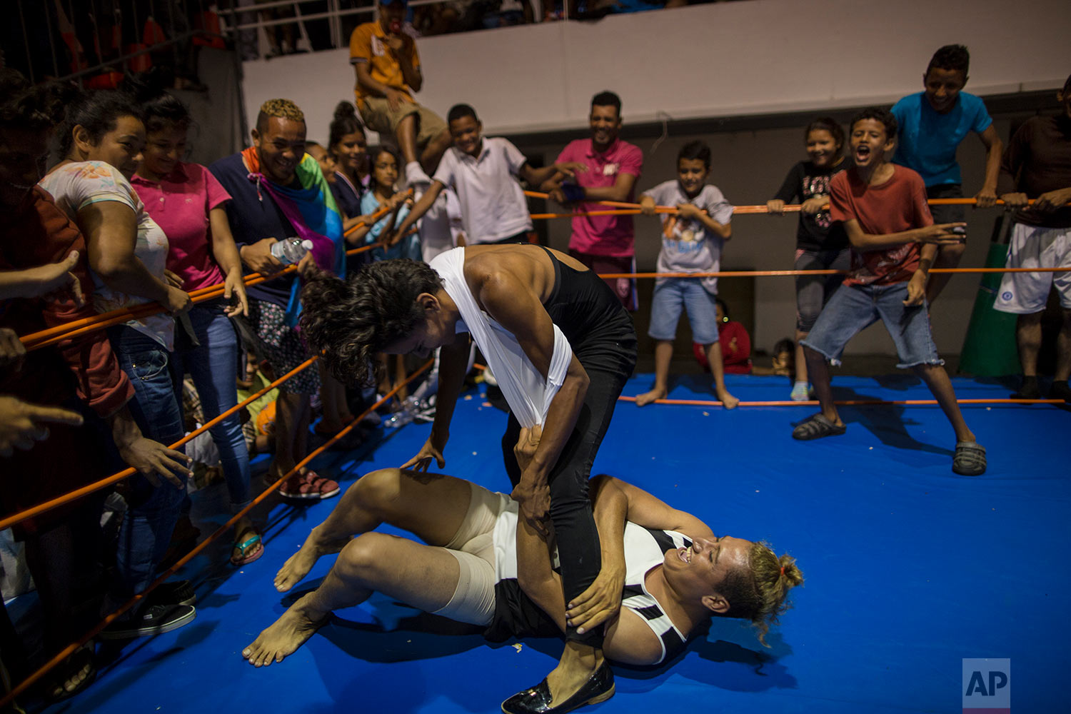 In this Nov. 4, 2018 photo, Nicaraguan transgender Sinai Cortez wrestles with her colleague Estrellita, of Honduras, because they were pressured by the men to get in the ring and battle it out, at a temporary shelter in Cordoba, Mexico. (AP Photo/Rodrigo Abd)