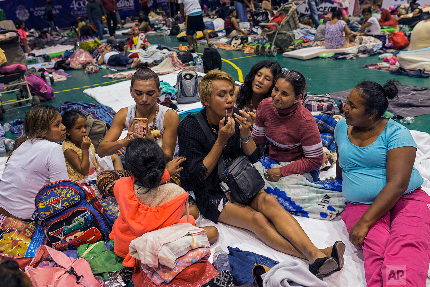 In this Nov. 4, 2018 photo, two transgender women who are part of a group of 50 or so LGBTQ migrants traveling with the migrant caravan hoping to reach the U.S. border, apply face makeup at a shelter in Cordoba, Mexico. (AP Photo/Rodrigo Abd)