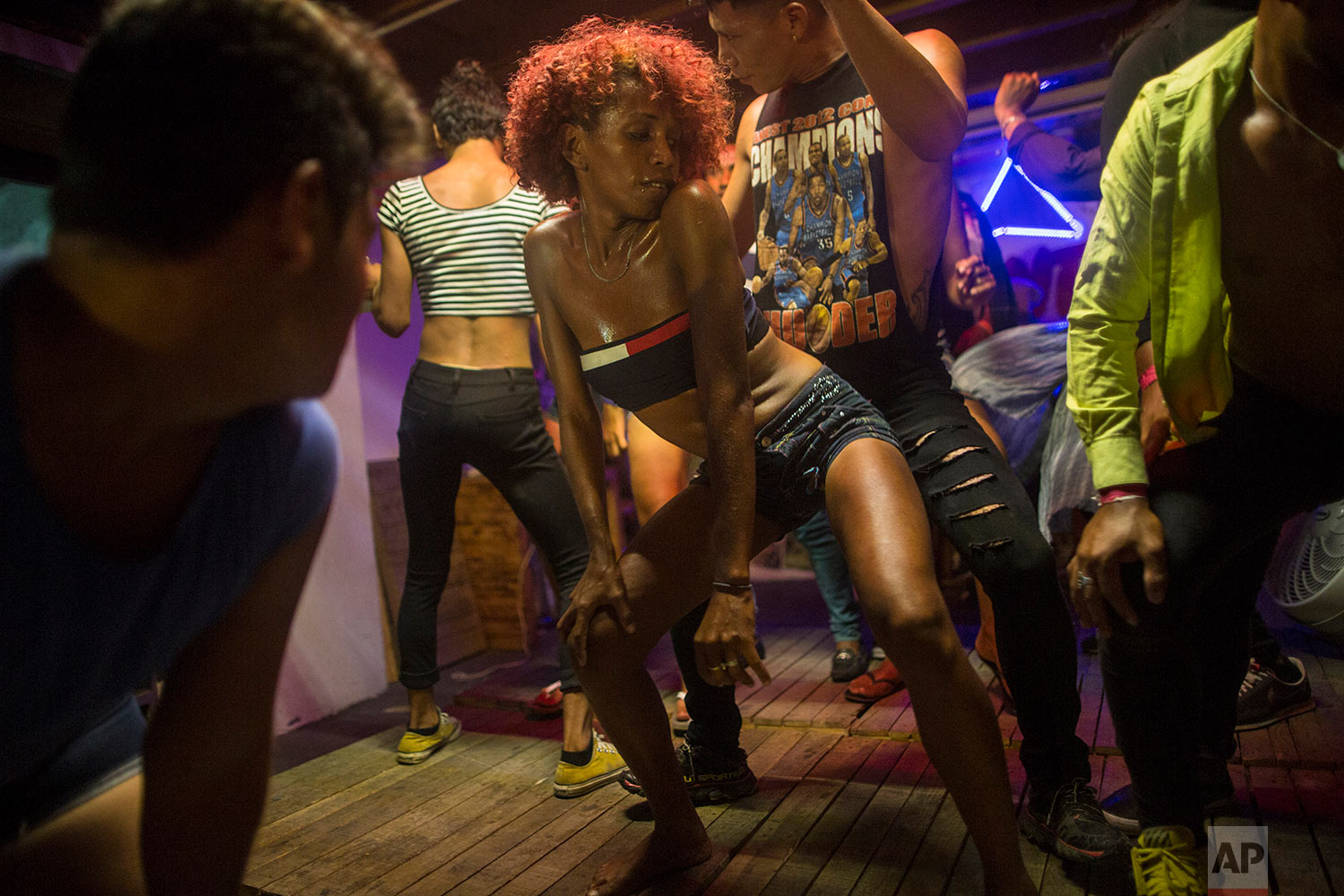 In this Nov. 8, 2018 photo, transgender Alexa Amaya, from Honduras, dances with colleagues in Mexico City, during a rest day for the Central American caravan hoping to reach the U.S. border. (AP Photo/Rodrigo Abd)
