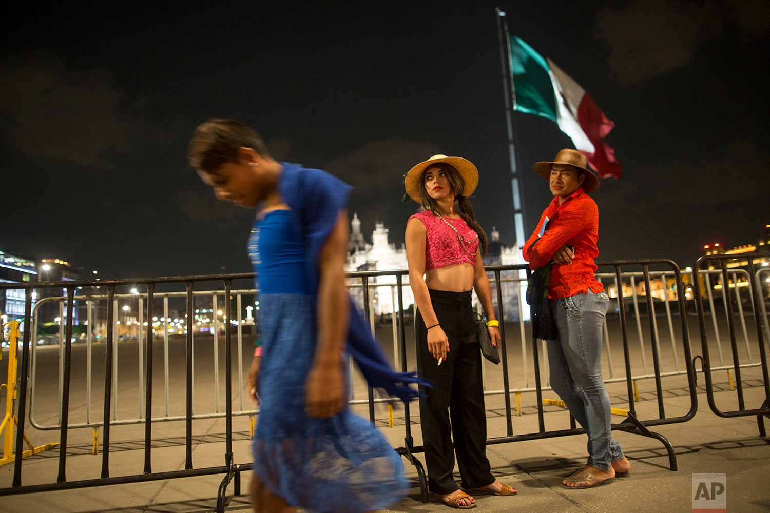 In this Nov. 6, 2018 photo, Honduran transgenders Alison Marisela, 19, from left, Naty Banegas, 16, and Nelsy Teresa Ponce, who are part of a group of 50 or so LGBTQ migrants  traveling with the Central American migrants caravan hoping to reach the U.S. border, visit the Zocalo, during a rest day for the migrants, in Mexico City. (AP Photo/Rodrigo Abd)