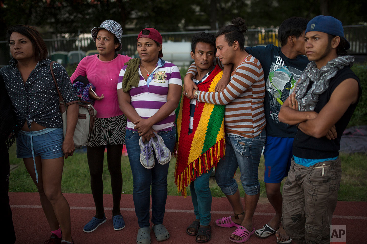 In this Nov. 4, 2018 photo, members of a group of 50 or so LGBTQ migrants, stand on the race track at the Jesus Martinez stadium that was  turned into a makeshift shelter, in Mexico City. (AP Photo/Rodrigo Abd)
