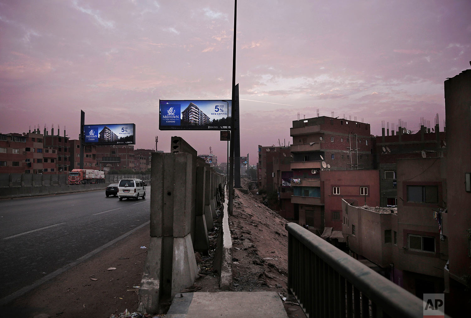 In this Oct. 23, 2018 photo, billboards promoting a new residential housing compound overlook a crowded run-down neighborhood, on the ring road, in Cairo, Egypt. (AP Photo/Nariman El-Mofty)