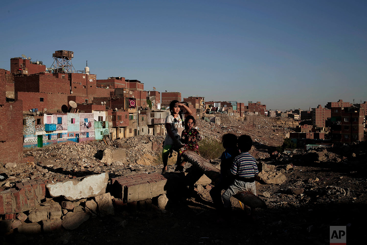 In this Oct. 28, 2018 photo, children play on a make shift see-saw made out of a tree trunk in slum area Ezbet Khairallah, Cairo, Egypt. (AP Photo/Nariman El-Mofty)