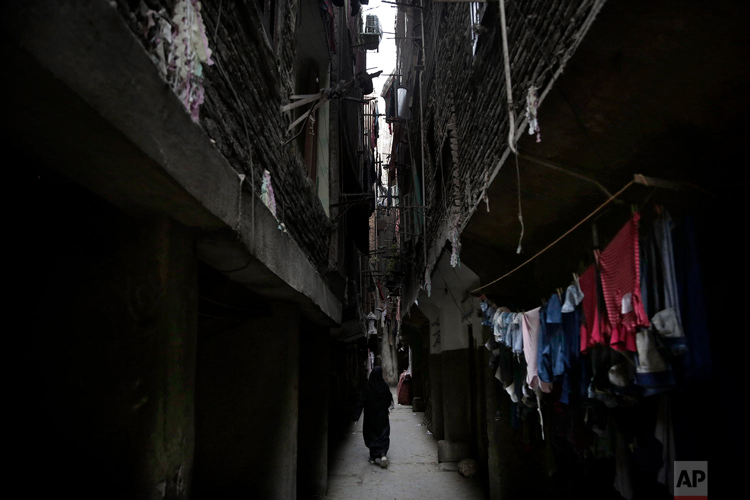 In this Oct. 29, 2018 photo, a woman walks in between buildings in the Imbaba neighborhood of Giza, Egypt. (AP Photo/Nariman El-Mofty)