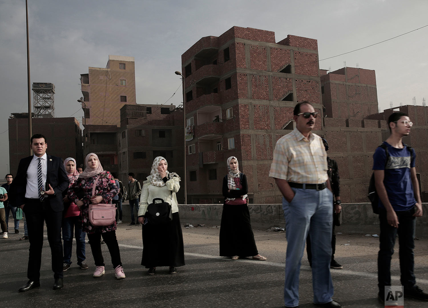 In this Oct. 23, 2018 photo, people wait for a bus on the ring road early morning, in Cairo, Egypt. (AP Photo/Nariman El-Mofty)