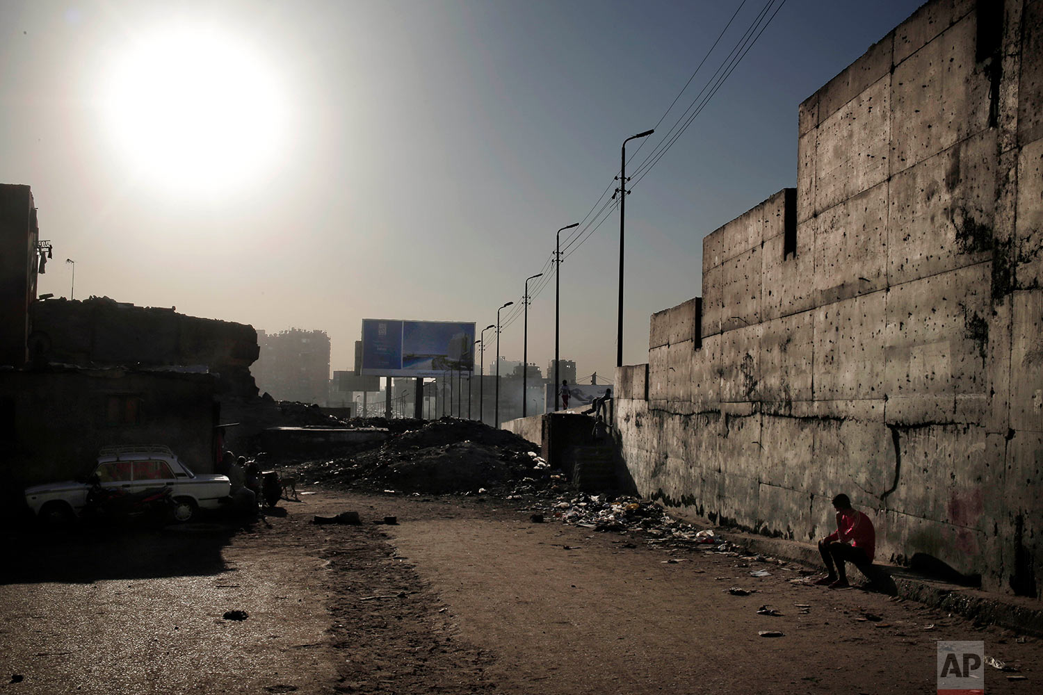 In this Oct. 28, 2018 photo, a man sits under a wall that separates the ring road from slum area Ezbet Khairallah, in Cairo, Egypt. (AP Photo/Nariman El-Mofty)