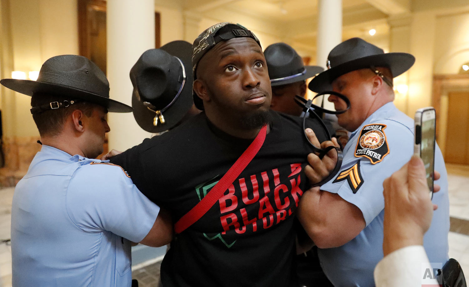 A man is arrested by Georgia state troopers during a protest over election ballot counts in the rotunda of the state Capitol building Tuesday, Nov. 13, 2018, in Atlanta. Several protesters, including a state senator, have been arrested during a demonstration at the Georgia state Capitol calling for tallying of uncounted ballots from the previous week's election. (AP Photo/John Bazemore)