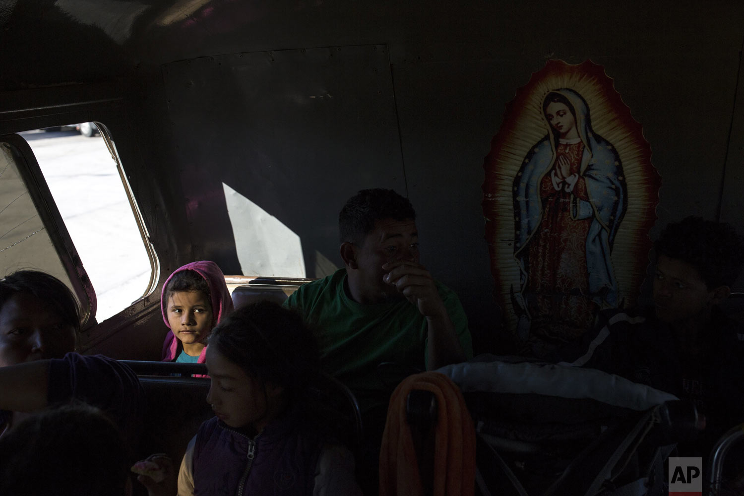 Genesis Mejia, 7, who is part of the Central American caravan hoping to reach the U.S. border, sits inside a bus in La Concha, Mexico, Wednesday, Nov. 14, 2018. Buses and trucks are carrying some migrants into the state of Sinaloa along the Gulf of California and further northward into the border state of Sonora. The bulk of the main caravan appeared to be about 1,100 miles from the border, but was moving hundreds of miles per day. At right is an image of the Virgin of Guadalupe. (AP Photo/Rodrigo Abd)