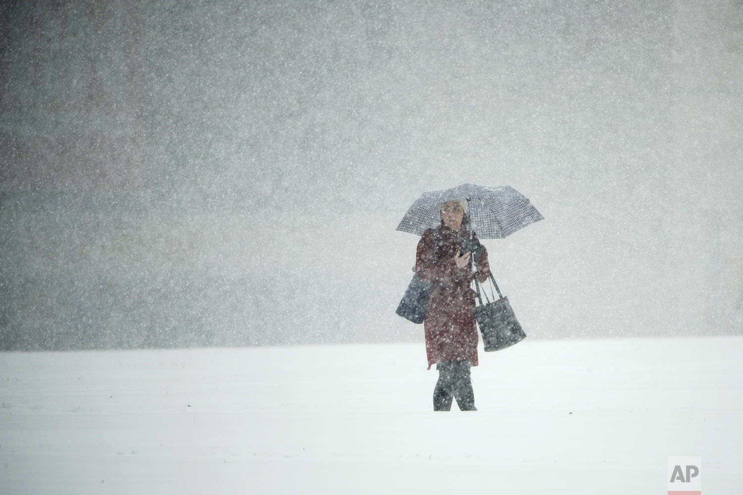 A person walks across Independence Mall during a snow storm in Philadelphia, Thursday, Nov. 15, 2018. (AP Photo/Matt Rourke)