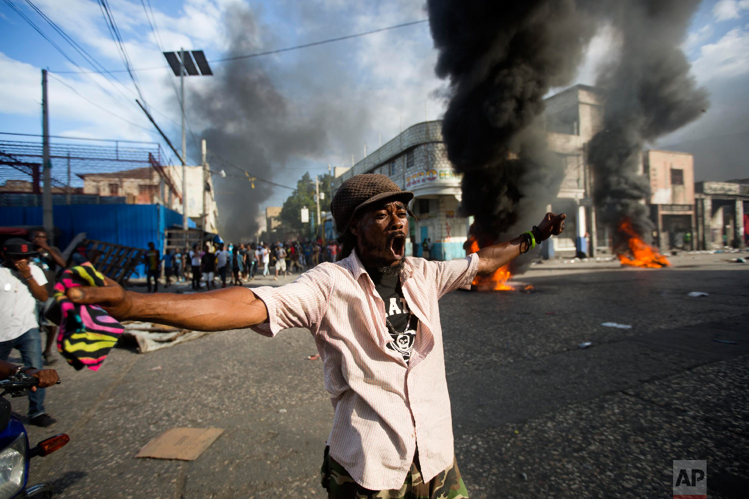 A demonstrator chants anti-government slogans during a protest demanding to know how Petro Caribe funds have been used by the current and past administrations, on the sidelines of events marking the 215th anniversary of independence Battle of Vertieres in Port-au-Prince, Haiti, Sunday, Nov. 18, 2018. (AP Photo/Dieu Nalio Chery)