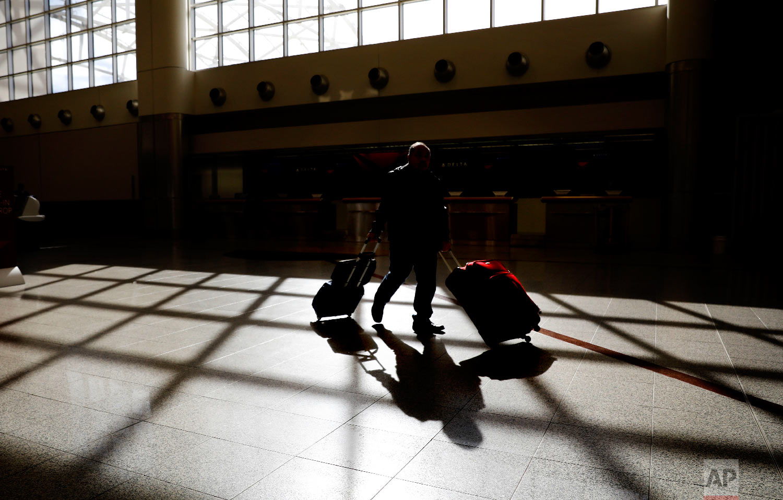A traveler wheels his luggage through Hartsfield-Jackson Atlanta International Airport on Thanksgiving in Atlanta, Thursday, Nov. 22, 2018. (AP Photo/David Goldman)