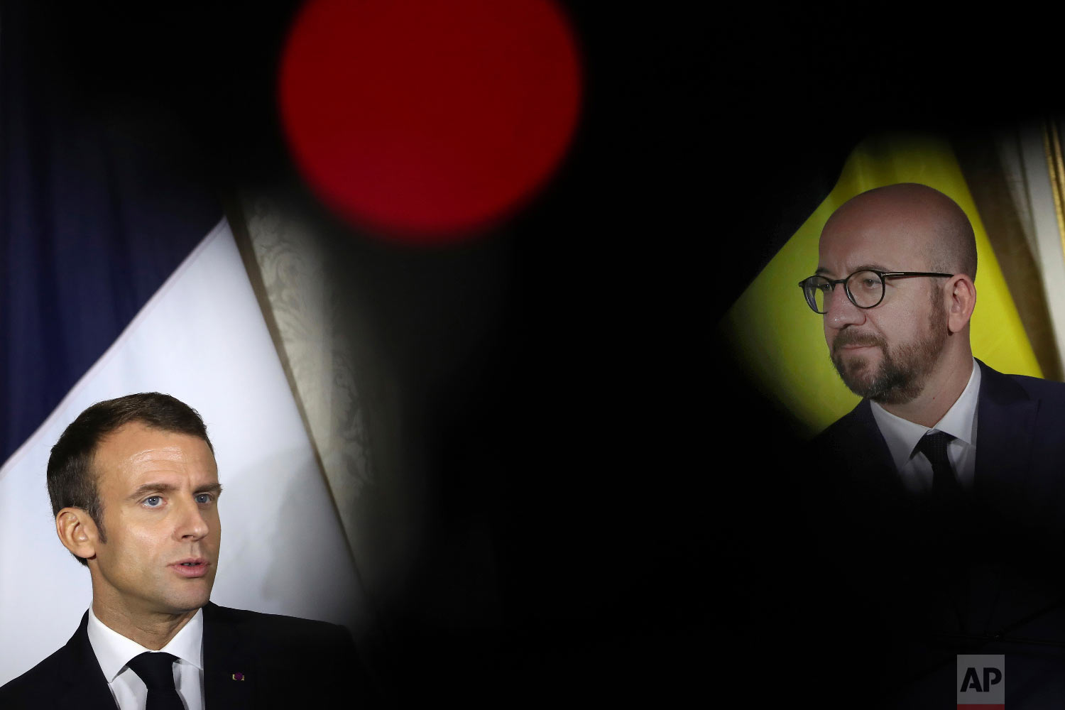 French President Emmanuel Macron, left, talks to journalists during a joint news conference with Belgian Prime Minister Charles Michel, right, following their meeting at the Egmont Palace in Brussels, Monday, Nov. 19, 2018.  (AP Photo/Francisco Seco)