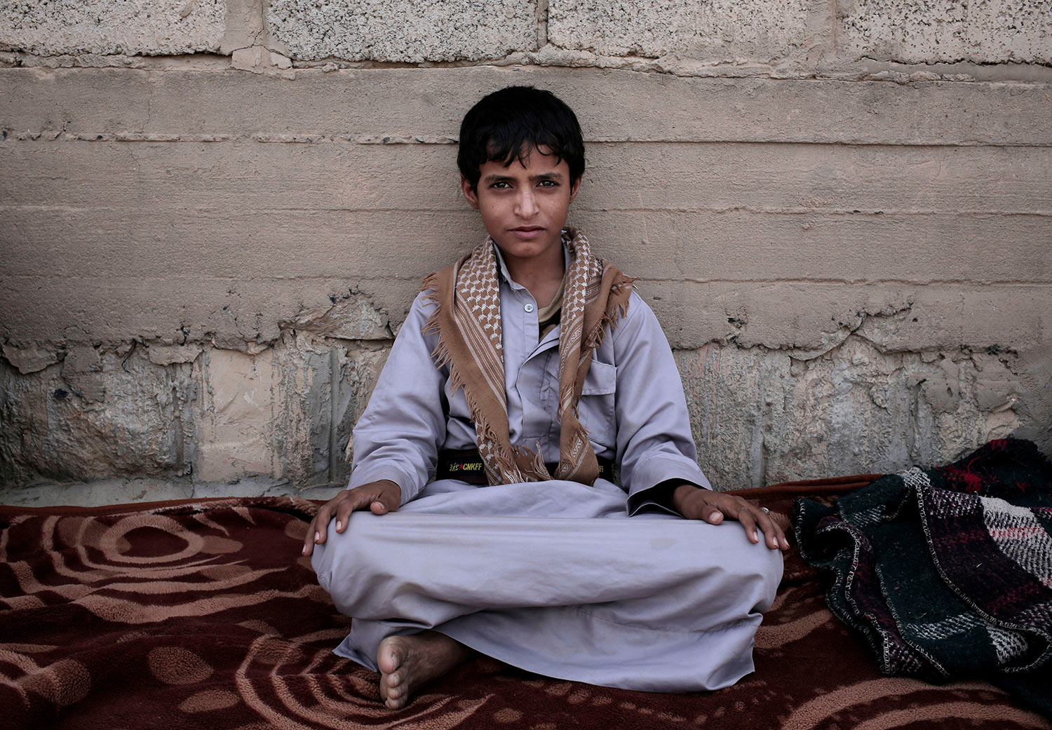 In this July 27, 2018 photo, 14 year-old Abdel Hamid Saleh, poses for a photograph at a camp for displaced persons where he took shelter, in Marib, Yemen. (AP Photo/Nariman El-Mofty)