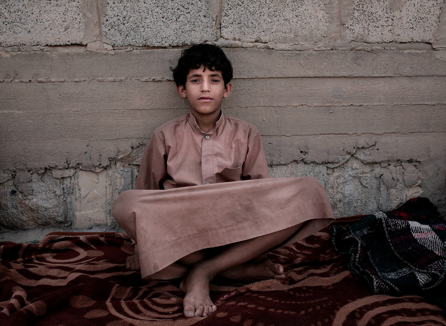 In this July 27, 2018 photo, 14 year-old Morsal Al Amery, poses for a photograph at a camp for displaced persons where he took shelter, in Marib, Yemen, (AP Photo/Nariman El-Mofty)