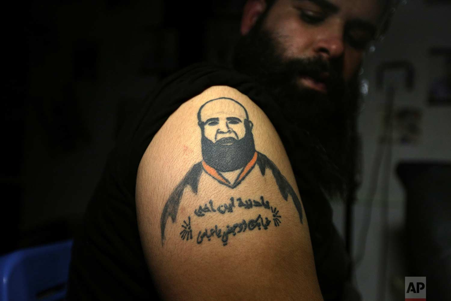 "In this Tuesday. Oct. 23, 2018, photo, Zuhair Atwan displays a tattoo of his brother, who was killed in sectarian violence, in a tattoo studio in Baghdad, Iraq. The Arabic sentence on his arm reads, ""Oh life, where is my brother? Your absence hurts me, oh Abbas."" (AP Photo/Hadi Mizban)"