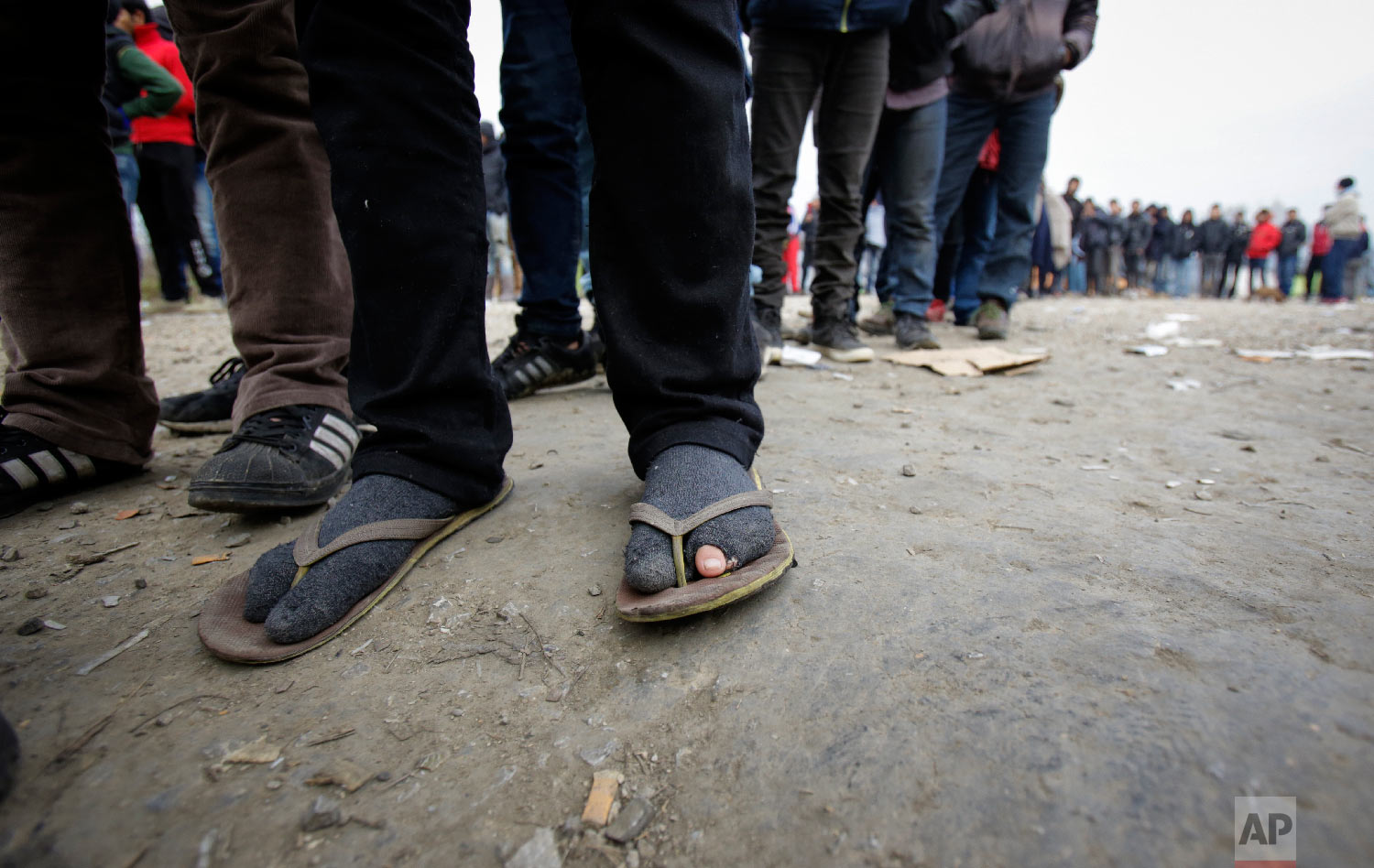 Migrants wearing tattered footwear wait in long lines for food distribution at a camp in Velika Kladusa, Bosnia, close to the border to Croatia, Sunday, Nov. 18, 2018. (AP Photo/Amel Emric)