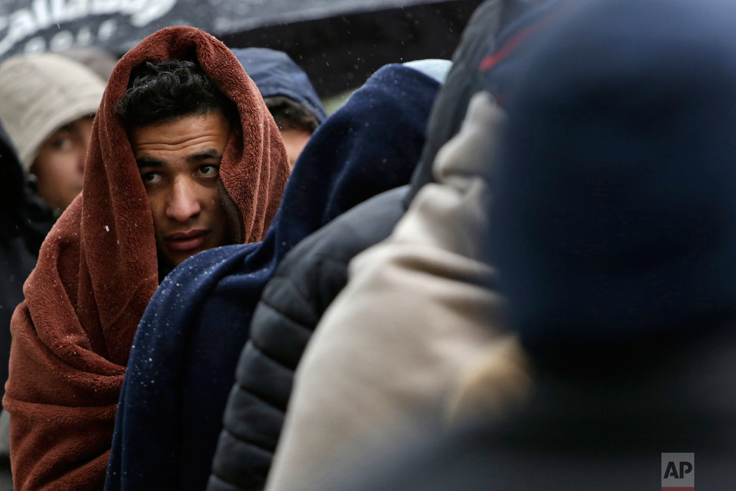 Migrants wrapped in blankets wait for food distribution in Bihac, Bosnia, close to the border to Croatia on Wednesday, Nov. 28, 2018. (AP Photo/Amel Emric)
