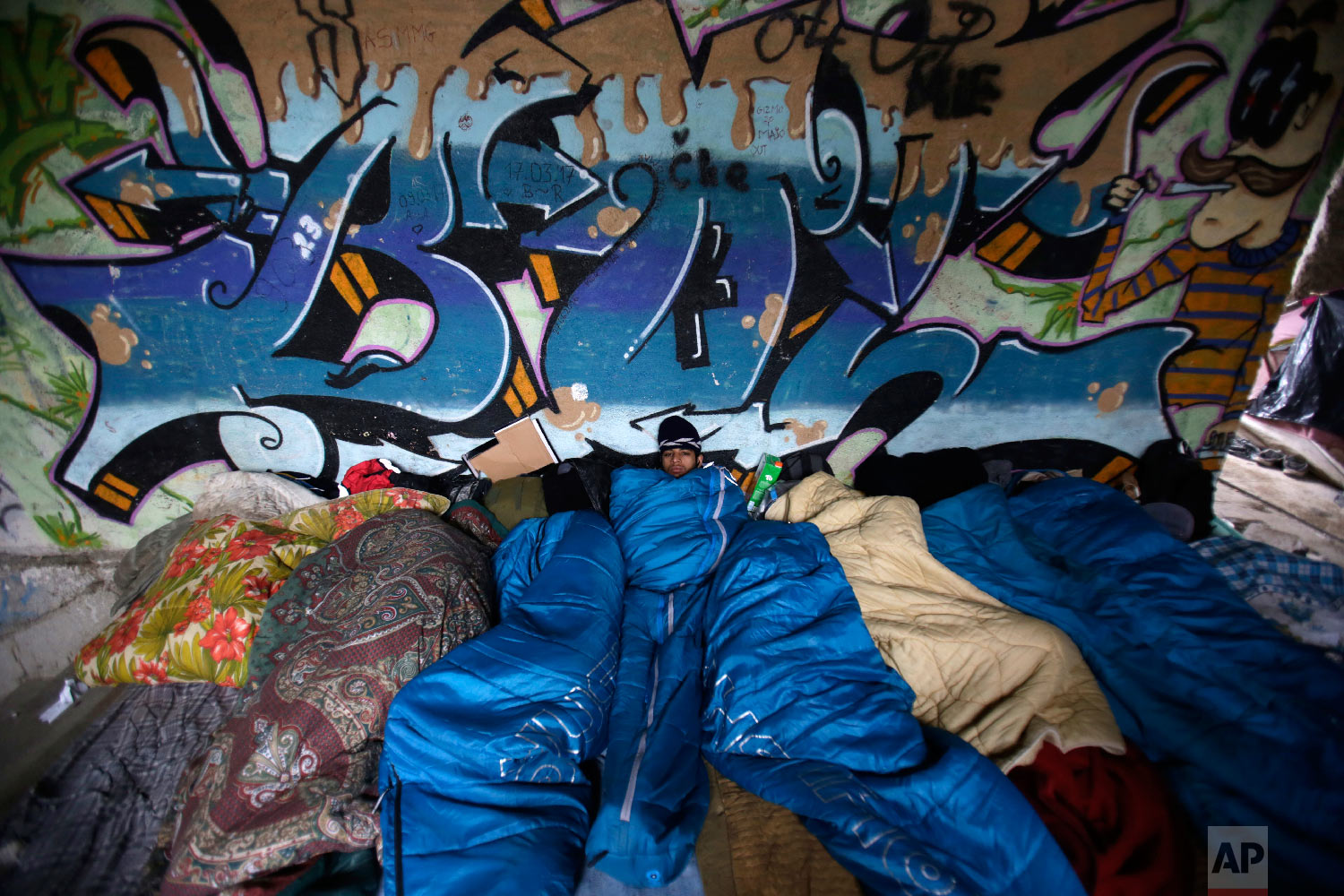 Migrants inside sleeping bags try to get warm, in Bihac, Bosnia, close to the border with Croatia on Wednesday, Nov. 28, 2018. (AP Photo/Amel Emric)