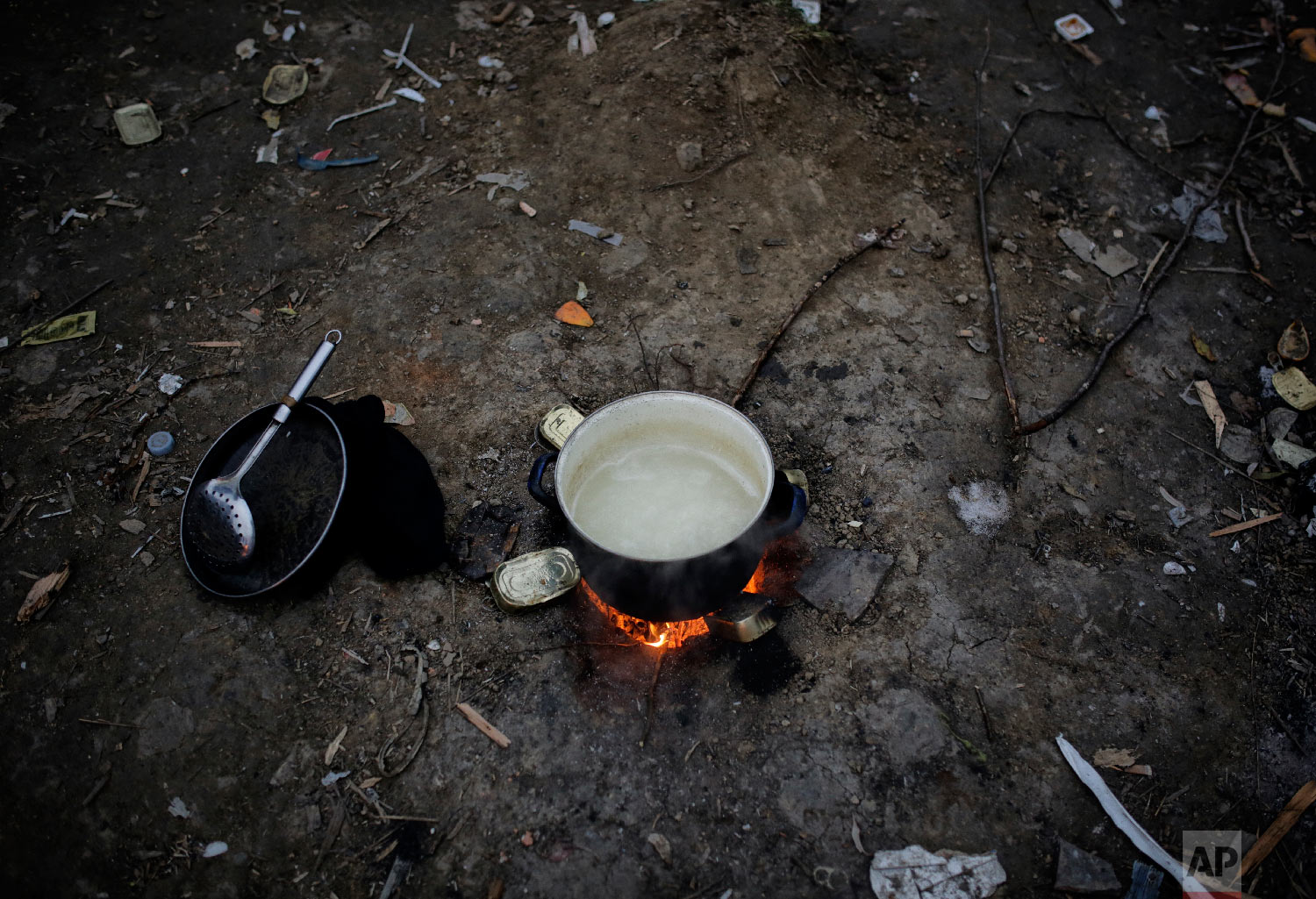 A cooking pot is placed on a fire outdoors at a camp in Velika Kladusa, Bosnia, close to the border to Croatia, Sunday, Nov. 18, 2018. (AP Photo/Amel Emric)