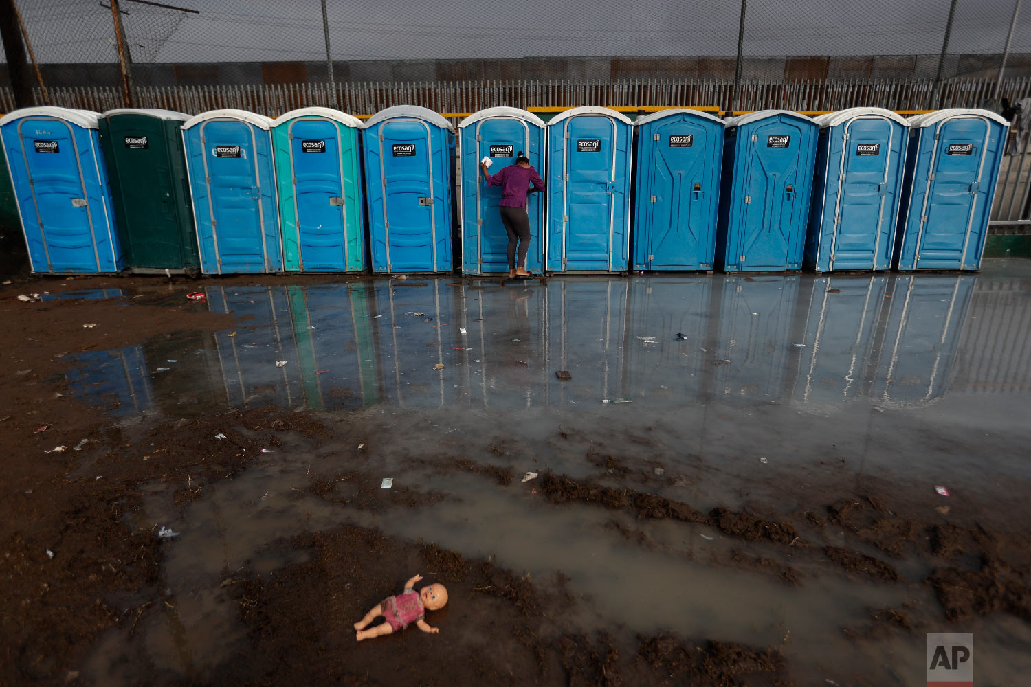 A woman searches a shower and rain flooded area for a toilet in acceptable condition at a sports complex sheltering thousands of Central Americans hoping to enter the U.S., in Tijuana, Mexico, Thursday, Nov. 29, 2018.  (AP Photo/Rebecca Blackwell)