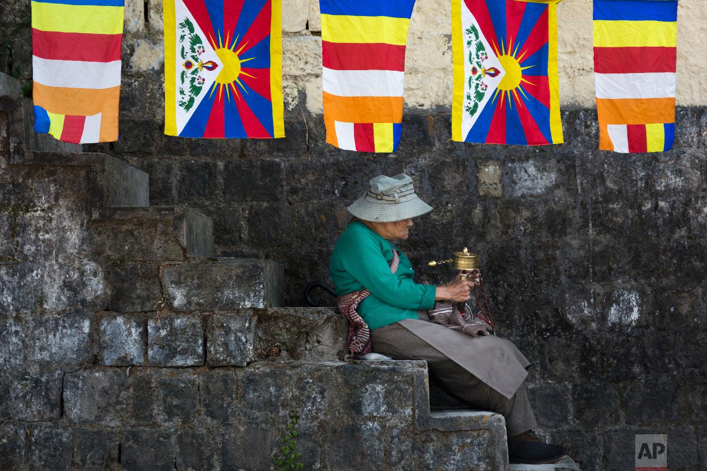 An exile Tibetan sits on the steps under a string of Tibetan and Buddhist flags as she waits to welcome her spiritual leader the Dalai Lama in Dharmsala, India, Sunday, Nov. 25, 2018.  (AP Photo /Ashwini Bhatia)