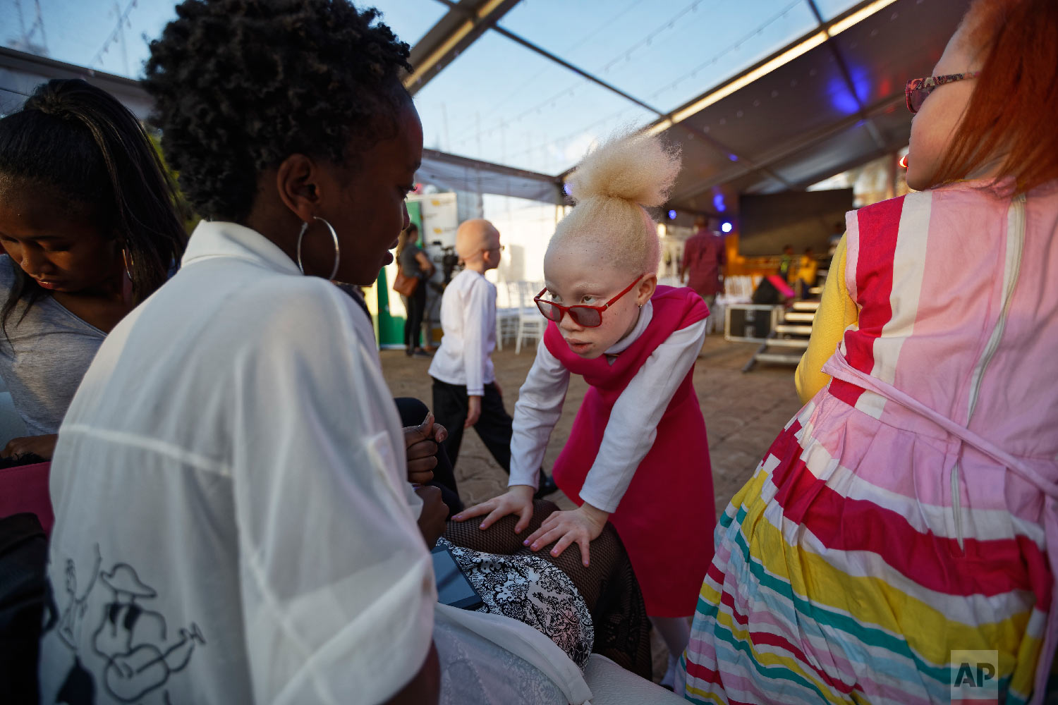 Albino girl Shirlyne 7, looks up at her aunt, left, and asks her to paint her nails as she waits for the start of the Mr. & Miss Albinism East Africa contest, organized by the Albinism Society of Kenya, in Nairobi, Kenya on Nov. 30, 2018. (AP Photo/Ben Curtis)