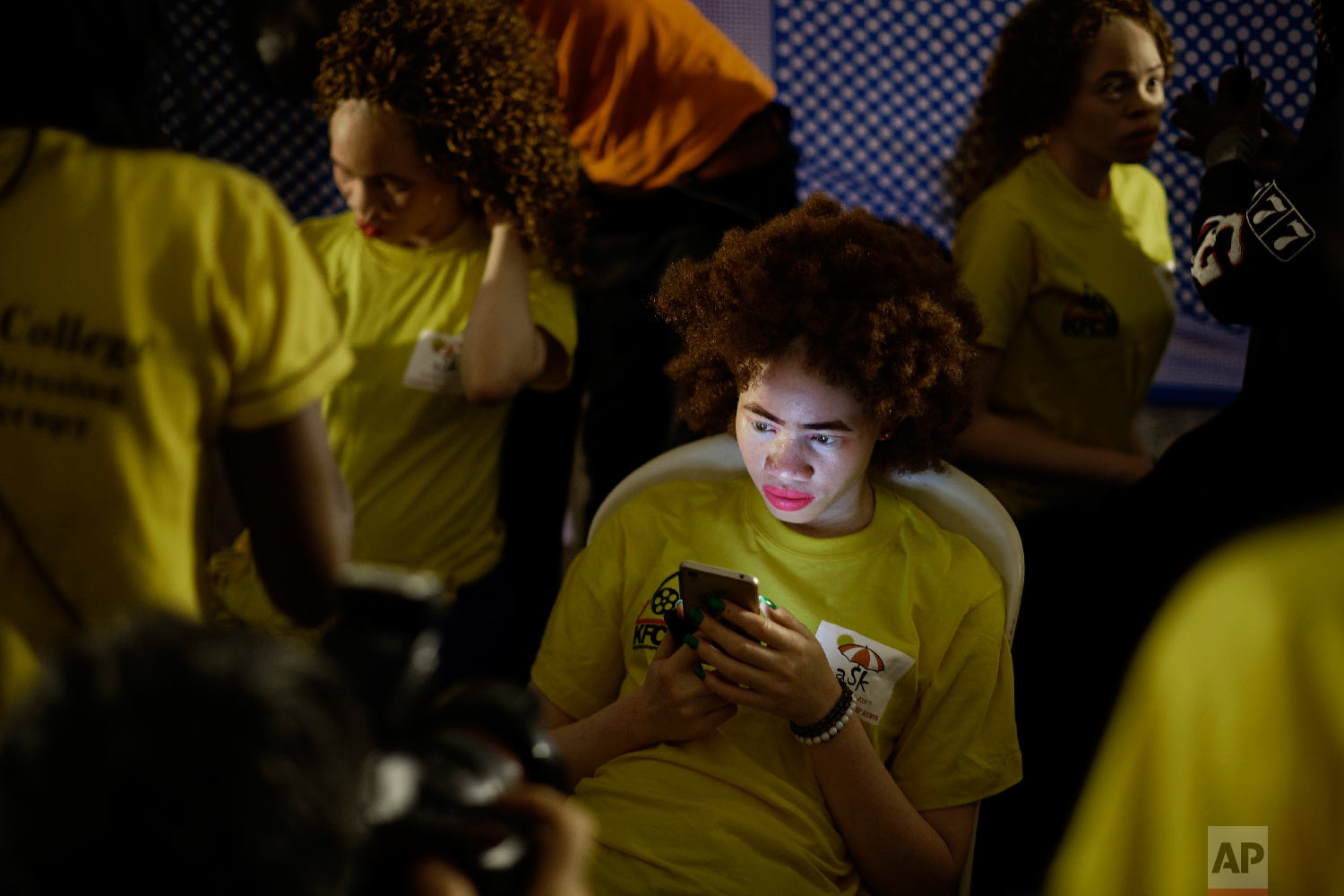 A contestant looks at her mobile phone after having her makeup done as she prepares for the start of the Mr. & Miss Albinism East Africa contest, organized by the Albinism Society of Kenya, in Nairobi, Kenya on Nov. 30, 2018. (AP Photo/Ben Curtis)