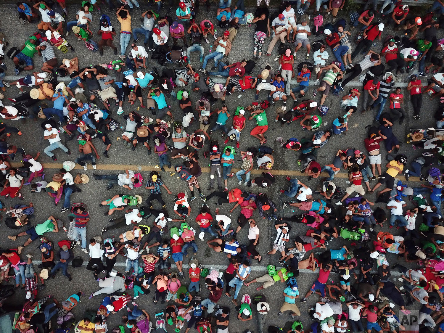 Members of a migrant caravan bound for the United States rest on a road between the Mexican states of Chiapas and Oaxaca after federal police briefly blocked them outside the town of Arriaga, on Oct. 27, 2018. (AP Photo/Rodrigo Abd)