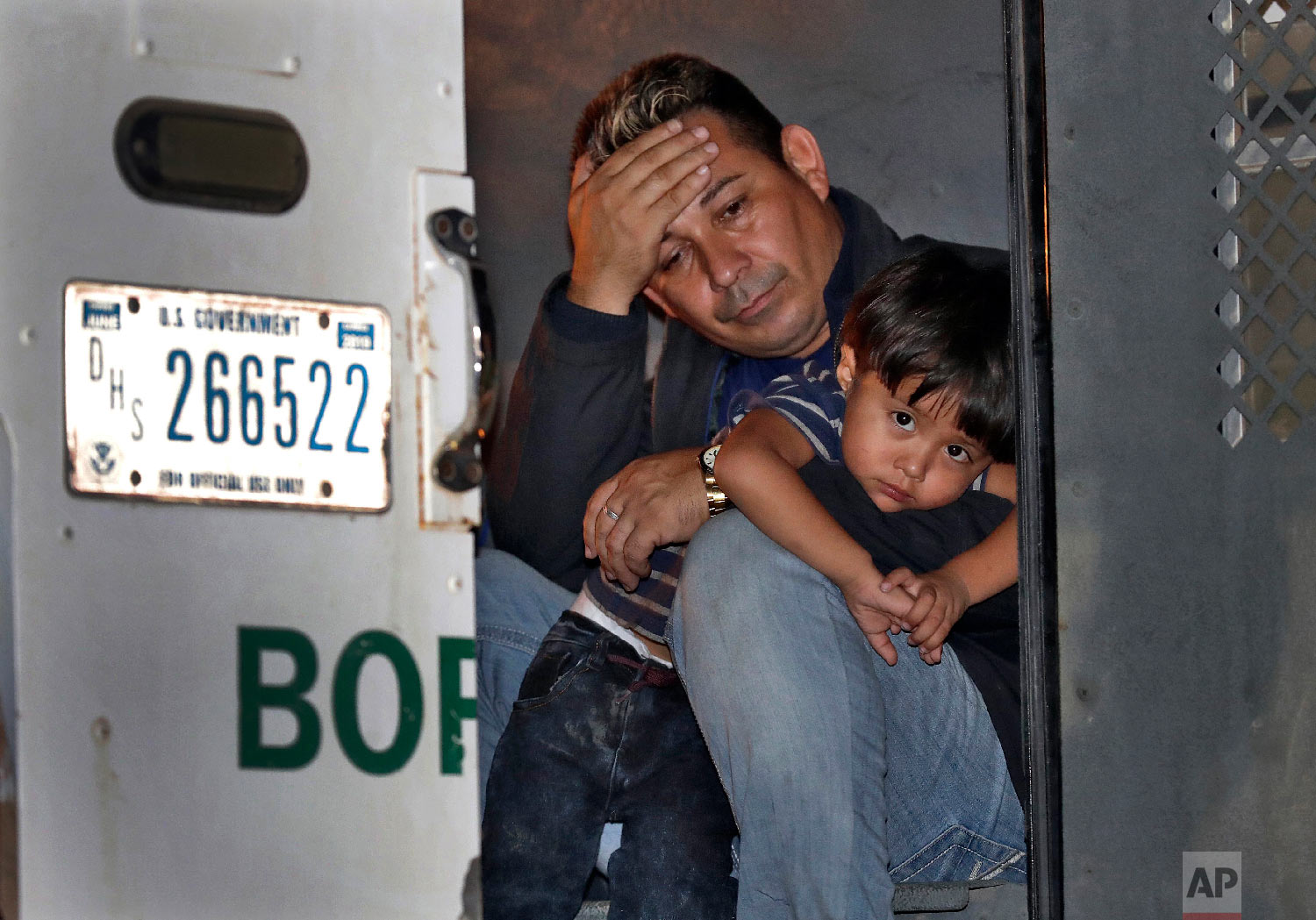 A father and his 3-year-old son are detained in the back of a U.S. Customs and Border Patrol vehicle on July 18, 2018, in San Luis, Ariz. The boy, his father and two siblings were arrested by a U.S. Border Patrol agent who spotted them crossing a canal along the the international border. (AP Photo/Matt York)