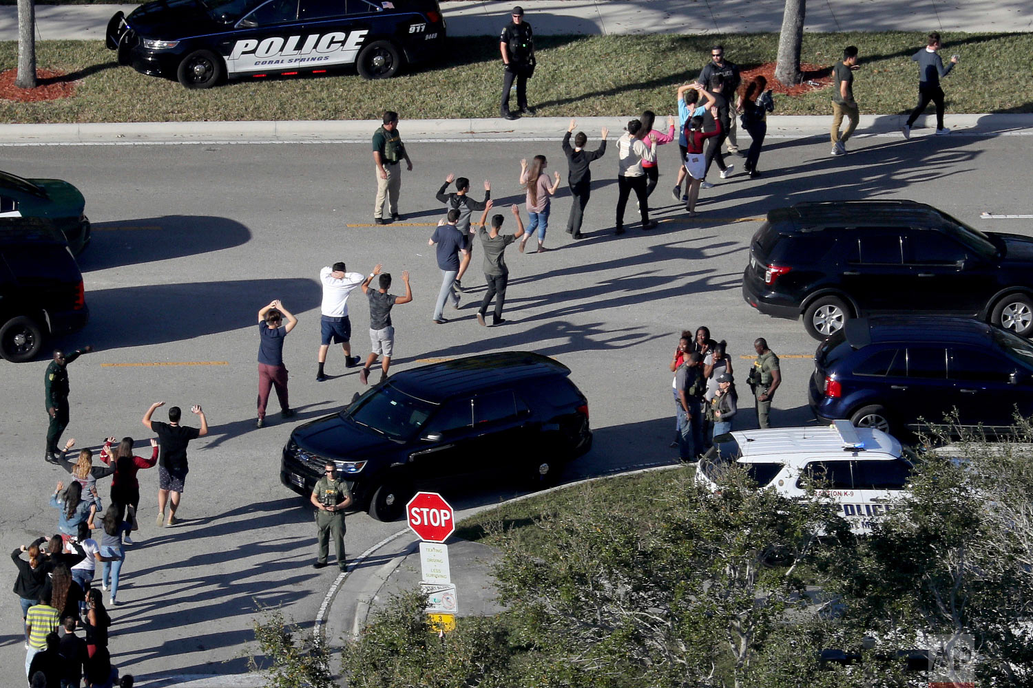 Students hold their hands in the air as they are evacuated by police from Marjory Stoneman Douglas High School in Parkland, Fla., on Feb. 14, 2018, after a shooter opened fire on the campus. (Mike Stocker/South Florida Sun-Sentinel via AP)