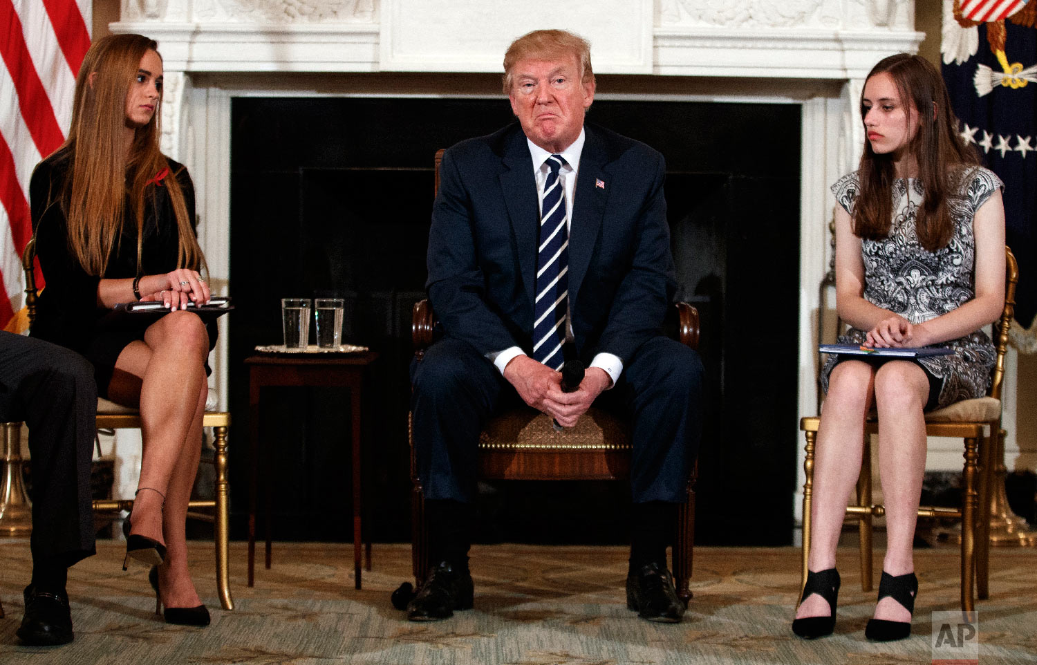 President Donald Trump, joined by Marjory Stoneman Douglas High School student Carson Abt, right, and Julia Cordover, the school's student body president, pauses during a listening session with high school students, teachers and others at the White House in Washington on Feb. 21, 2018, a week after a gunman massacred 17 people at the Florida high school. (AP Photo/Carolyn Kaster)