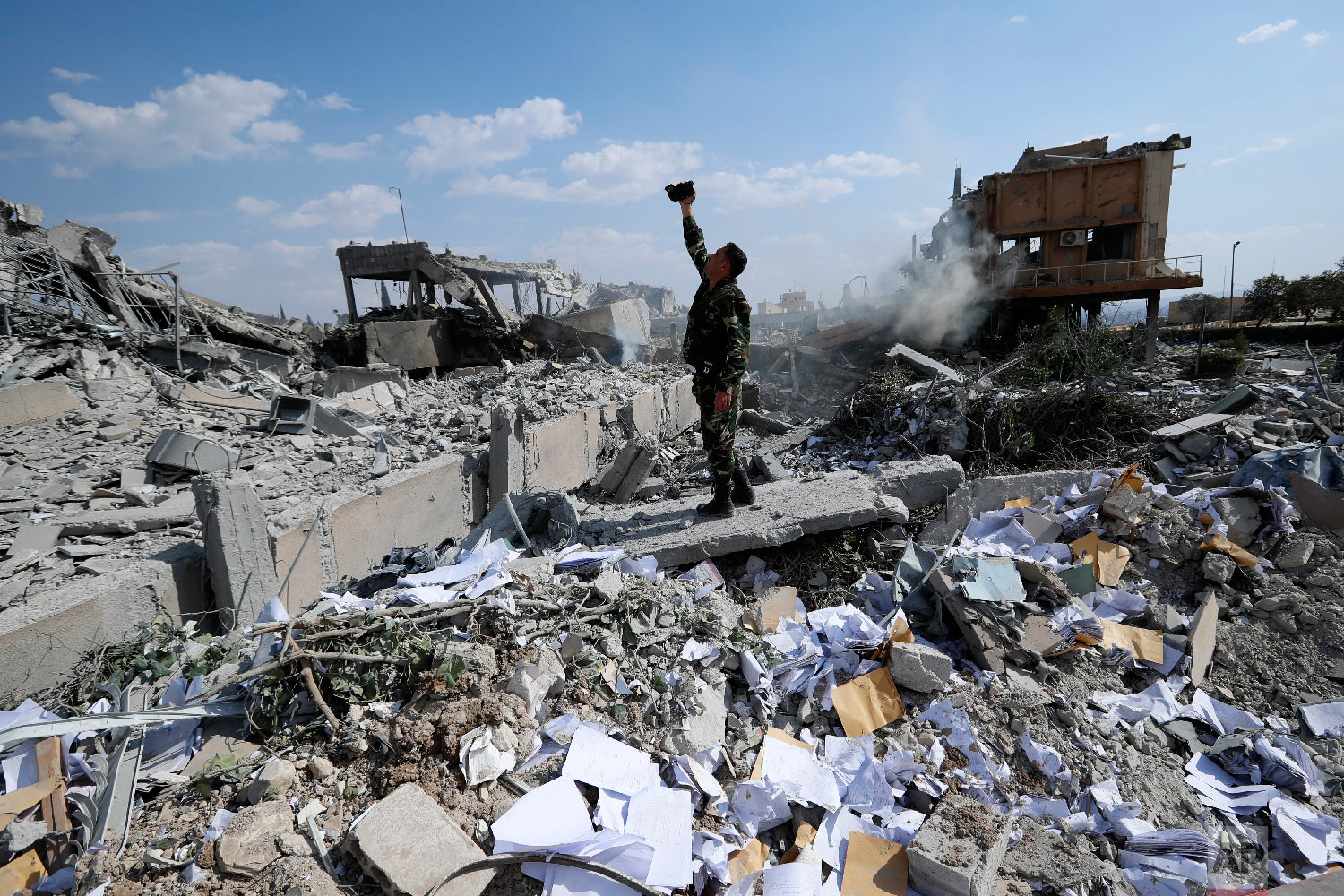 A Syrian soldier films the wreckage of the Syrian Scientific Research Center, which was attacked by U.S., British and French military strikes to punish President Bashar Assad for a suspected chemical attack against civilians, in the Damascus suburb of Barzeh, Syria, on April 14, 2018. (AP Photo/Hassan Ammar)