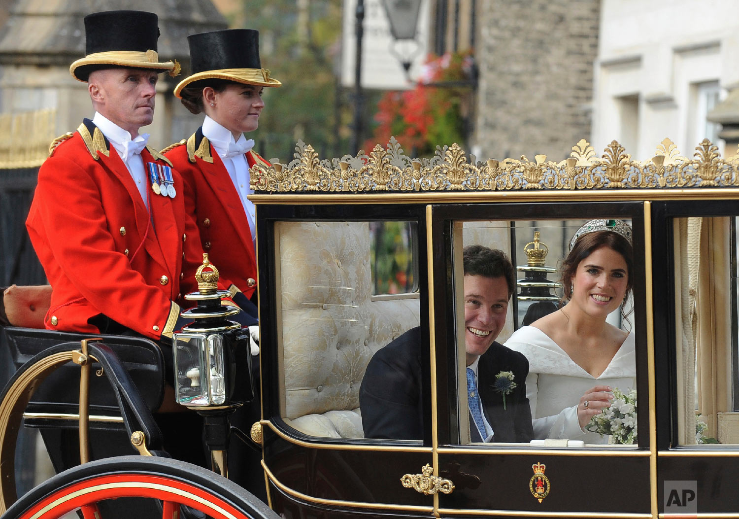 Princess Eugenie of York, right, and Jack Brooksbank look out from their carriage as they travel from St. George's Chapel to Windsor Castle after their wedding in Windsor, England, near London, on Oct. 12, 2018. (AP Photo/Rui Vieira)