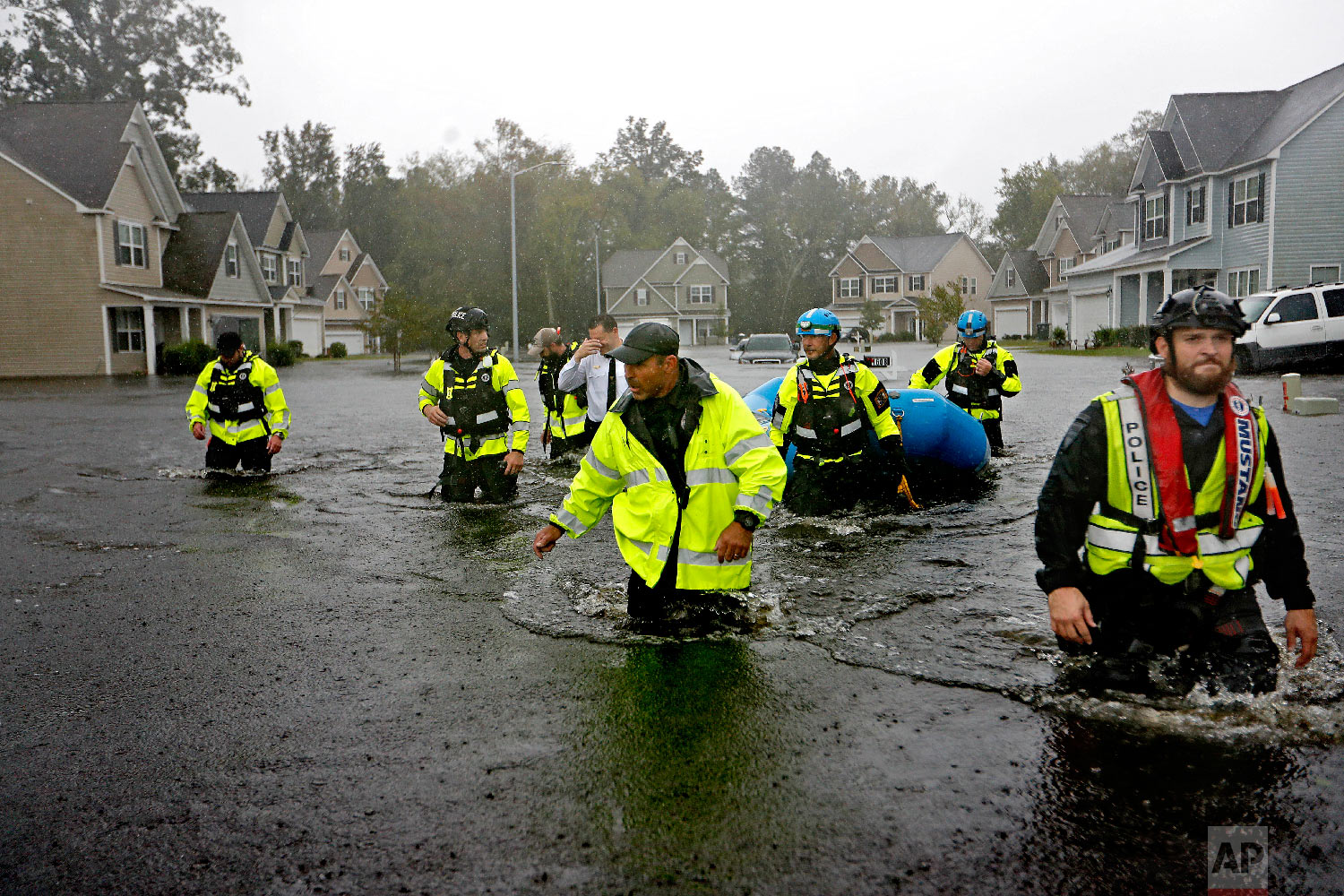 Members of the North Carolina Task Force urban search and rescue team wade through a flooded neighborhood looking for residents who stayed behind as Florence continues to dump heavy rain in Fayetteville, N.C., on Sept. 16, 2018. (AP Photo/David Goldman)