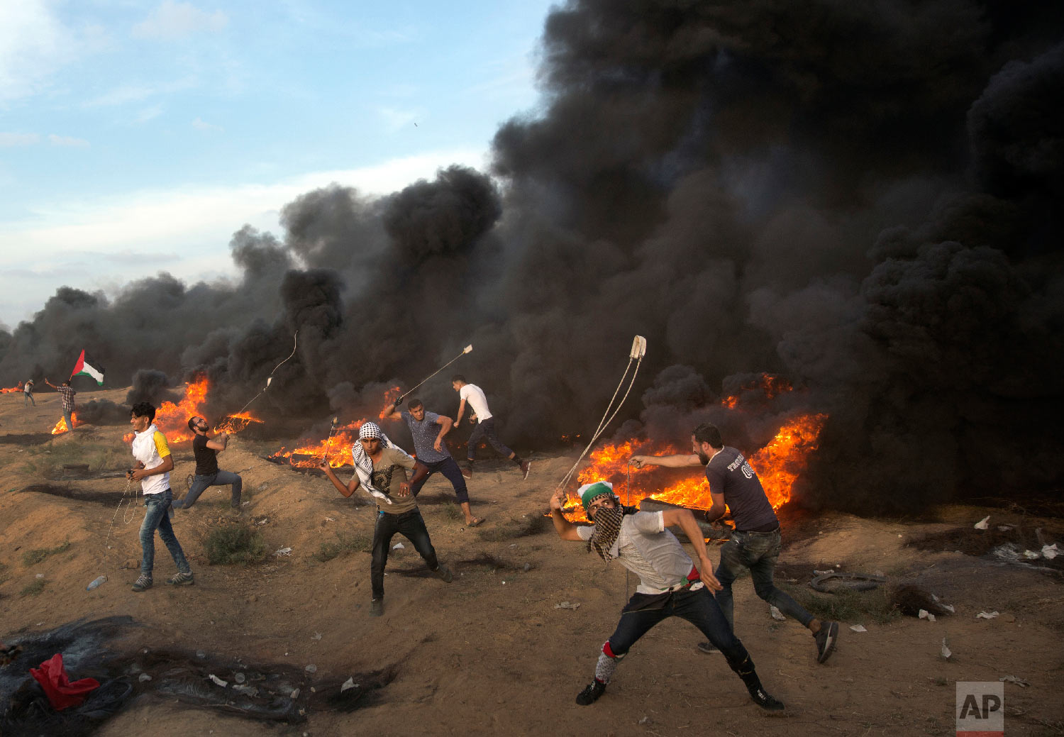 Palestinians hurl stones during a protest at the Gaza Strip's border with Israel on Oct. 5, 2018. (AP Photo/Khalil Hamra)
