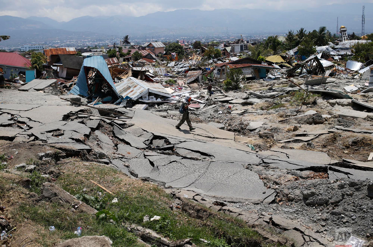 A man walks through the Balaroa neighborhood in Palu, Central Sulawesi, Indonesia, on Oct. 2, 2018, four days after a massive earthquake struck the region. (AP Photo/Dita Alangkara)
