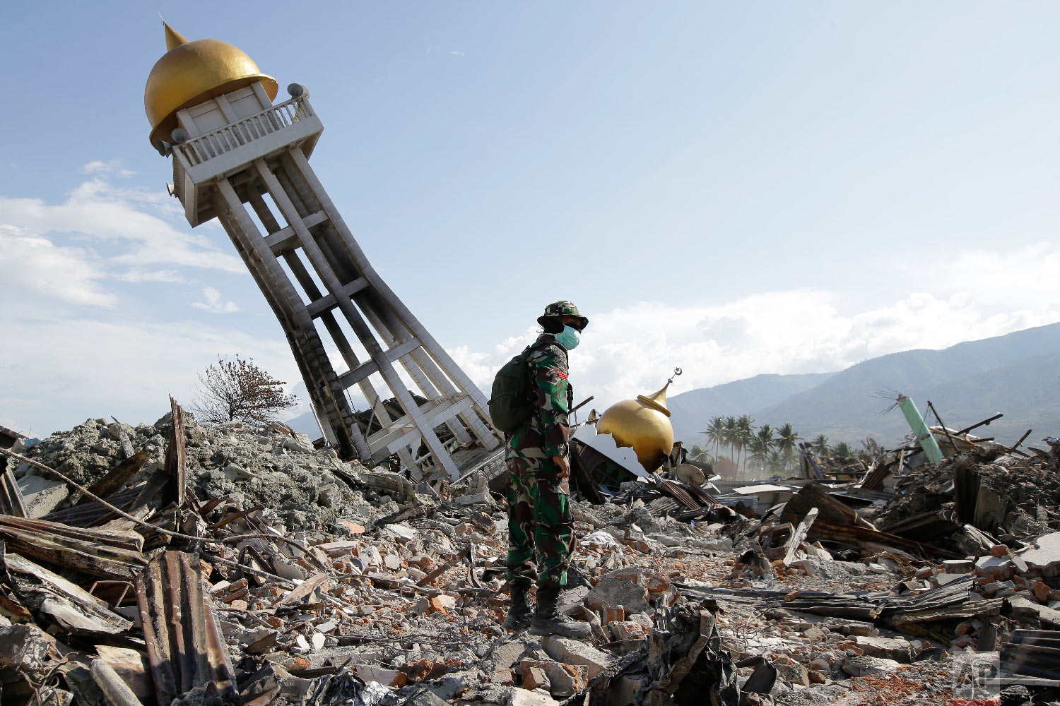 An Indonesian trooper stands beside a toppled mosque as recovery efforts continue at the earthquake-hit Balaroa neighborhood in Palu, Central Sulawesi, Indonesia, on Oct. 6, 2018. (AP Photo/Aaron Favila)