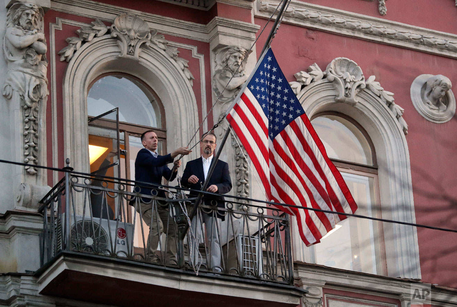 Employees at the U.S. consulate in St. Petersburg, Russia, remove the U.S flag on March 31, 2018, after Russia announced it was closing the consulate and expelling more than 150 diplomats, including 60 Americans. The move was in retaliation for the wave of Western expulsions of Russian diplomats over the poisoning of an ex-spy and his daughter in Britain. (AP Photo/Dmitri Lovetsky)