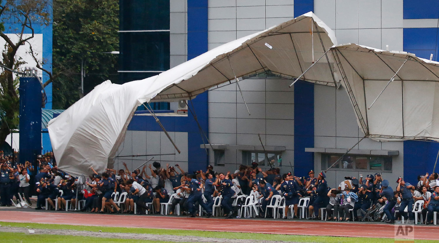 Philippine National Police officers and employees react as their tent is toppled by the downwash of a hovering police helicopter performing a salute during the 117th Philippine National Police Service anniversary at Camp Crame in Quezon City, a suburb of Manila, on Aug. 8, 2018. (AP Photo/Bullit Marquez)