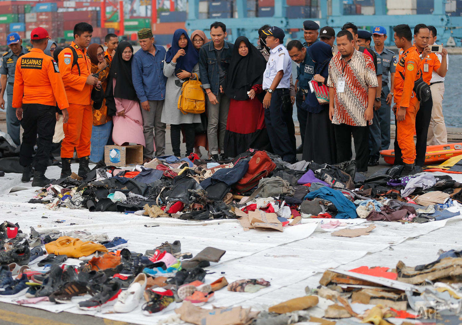 Relatives of passengers on the crashed Lion Air jet check personal belongings retrieved from the waters where the airplane is believed to have crashed, at Tanjung Priok Port in Jakarta, Indonesia, on Oct. 31, 2018. (AP Photo/Tatan Syuflana)