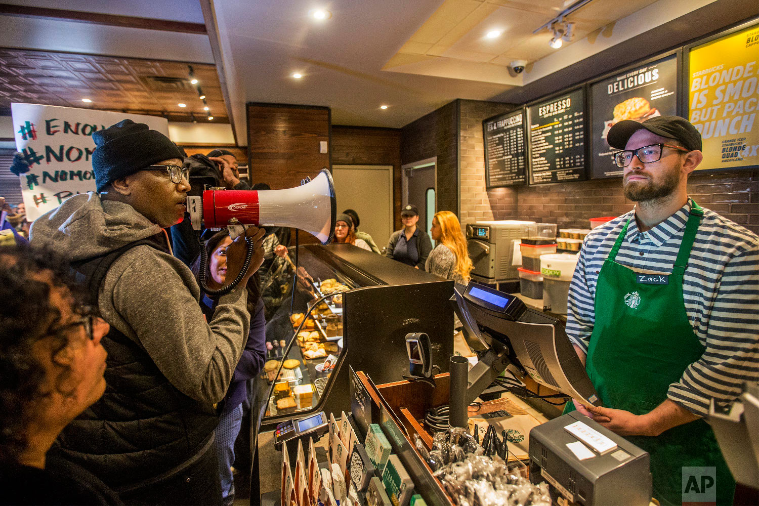 Local Black Lives Matter activist Asa Khalif, left, uses a megaphone inside a Starbucks on April 15, 2018, demanding the firing of the manager who called police on two black men who had entered the store, but didn't make a purchase, resulting in their arrest. The arrests were captured on video that quickly gained traction on social media. (Mark Bryant/The Philadelphia Inquirer via AP)