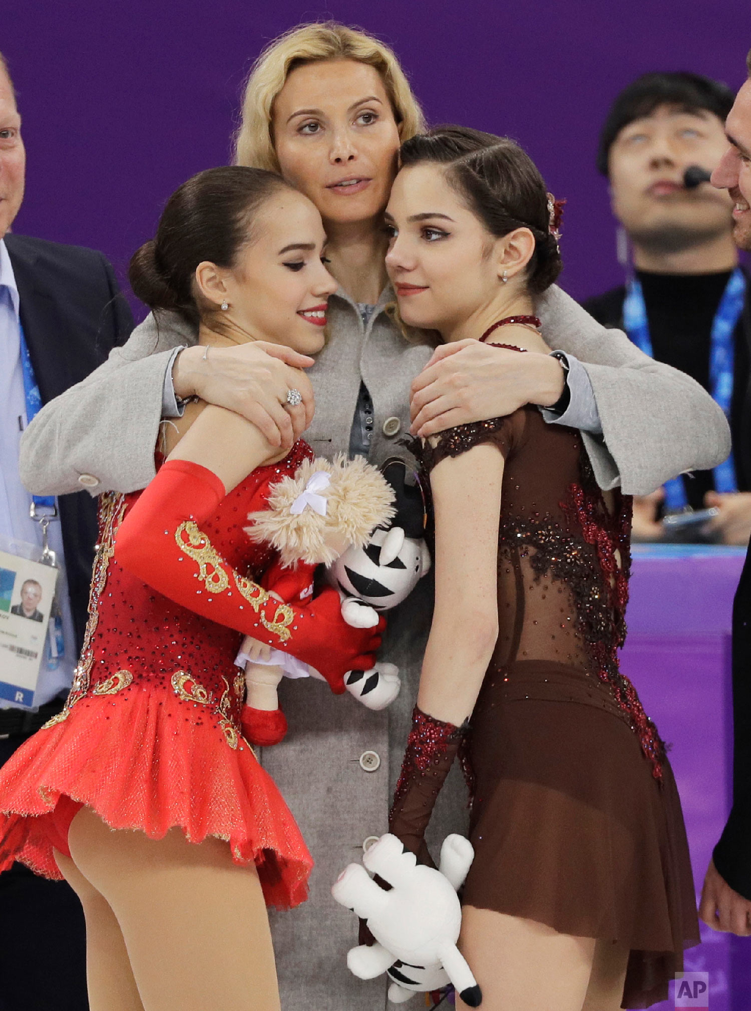 Gold medalist Alina Zagitova, left, and silver medalist Evgenia Medvedeva, both representing the Olympic Athletes of Russia (OAR), are embraced by their coach, Eteri Georgievna Tutberidze, at the women's free figure skating final at the 2018 Winter Olympics in Gangneung, South Korea, on Feb. 23, 2018.(AP Photo/David J. Phillip)