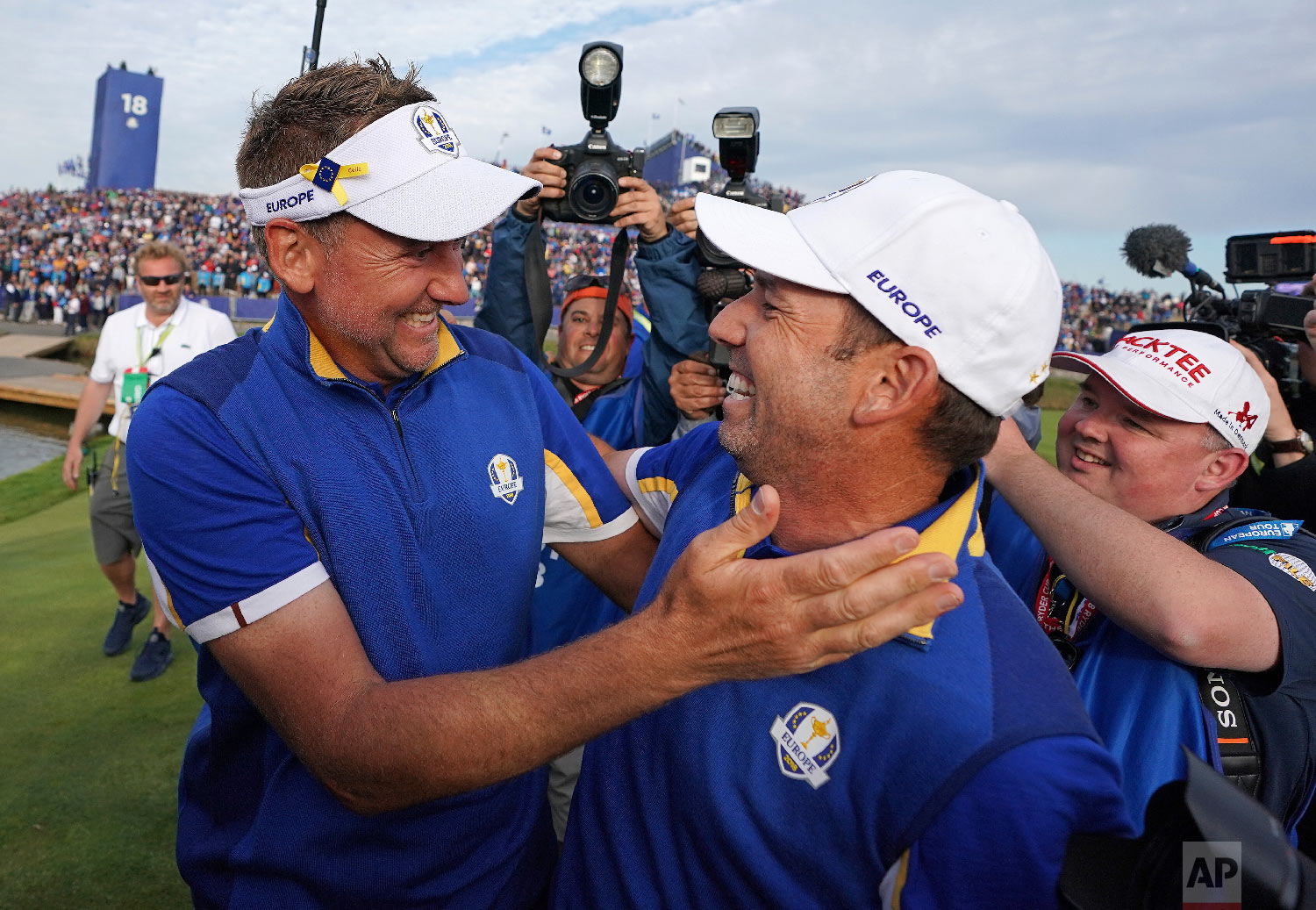 Europe's Sergio Garcia, right, celebrates with Ian Poulter after Europe won the Ryder Cup on the final day of the 42nd Ryder Cup at Le Golf National in Saint-Quentin-en-Yvelines, outside Paris, France, on Sept. 30, 2018. (AP Photo/Laurent Cipriani)