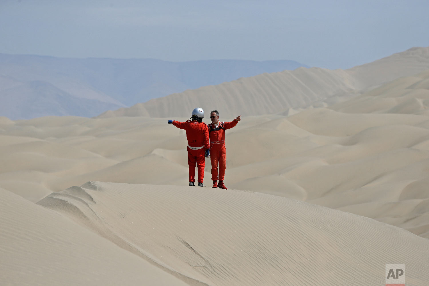 Philippe Raud, of France, right, and Miguel Angel Alvarez Pineda, of Peru, both drivers of Toyota cars, point in opposite directions as they try to determine their way across the dunes during stage 5 of the Dakar Rally between San Juan de Marcona and Arequipa, Peru, on Jan. 10, 2018. (AP Photo/Ricardo Mazalan)
