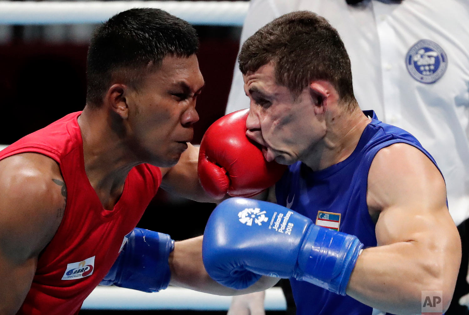 Phillippines' Eumir Felix Marcial, left, lands a blow on the face of Uzbekistan's Israil Madrimov during their men's middleweight boxing semifinal at the 18th Asian Games in Jakarta, Indonesia, on Aug. 31, 2018. (AP Photo/Lee Jin-man)