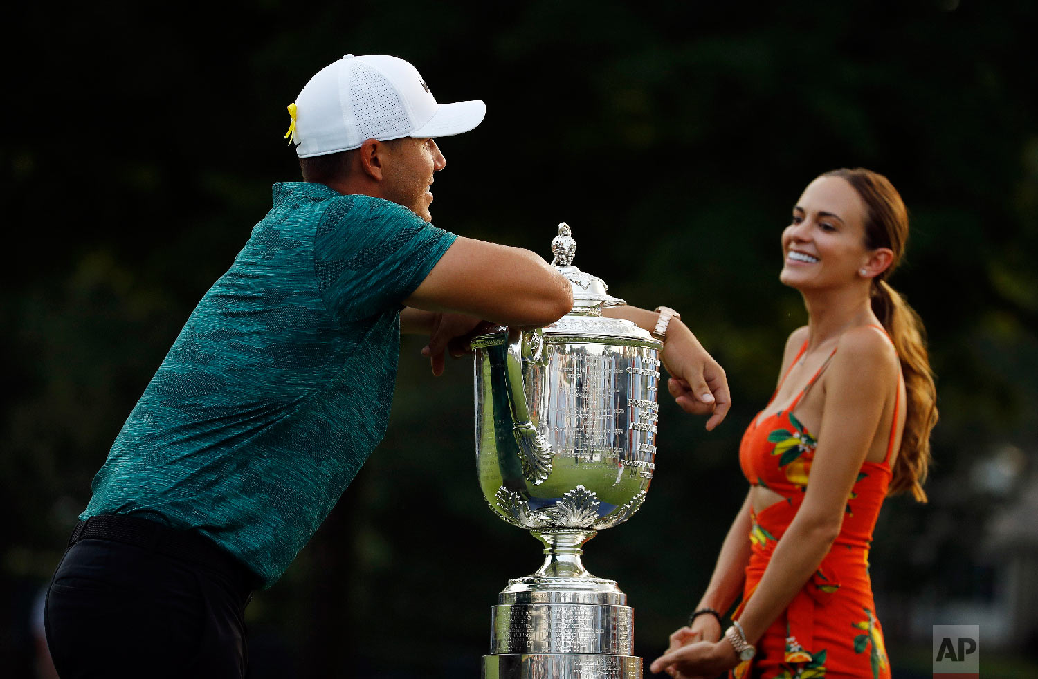 Brooks Koepka leans on the Wanamaker Trophy as he talks with his girlfriend, Jena Sims, after winning the PGA Championship golf tournament at Bellerive Country Club in St. Louis on Aug. 12, 2018. (AP Photo/Charlie Riedel)
