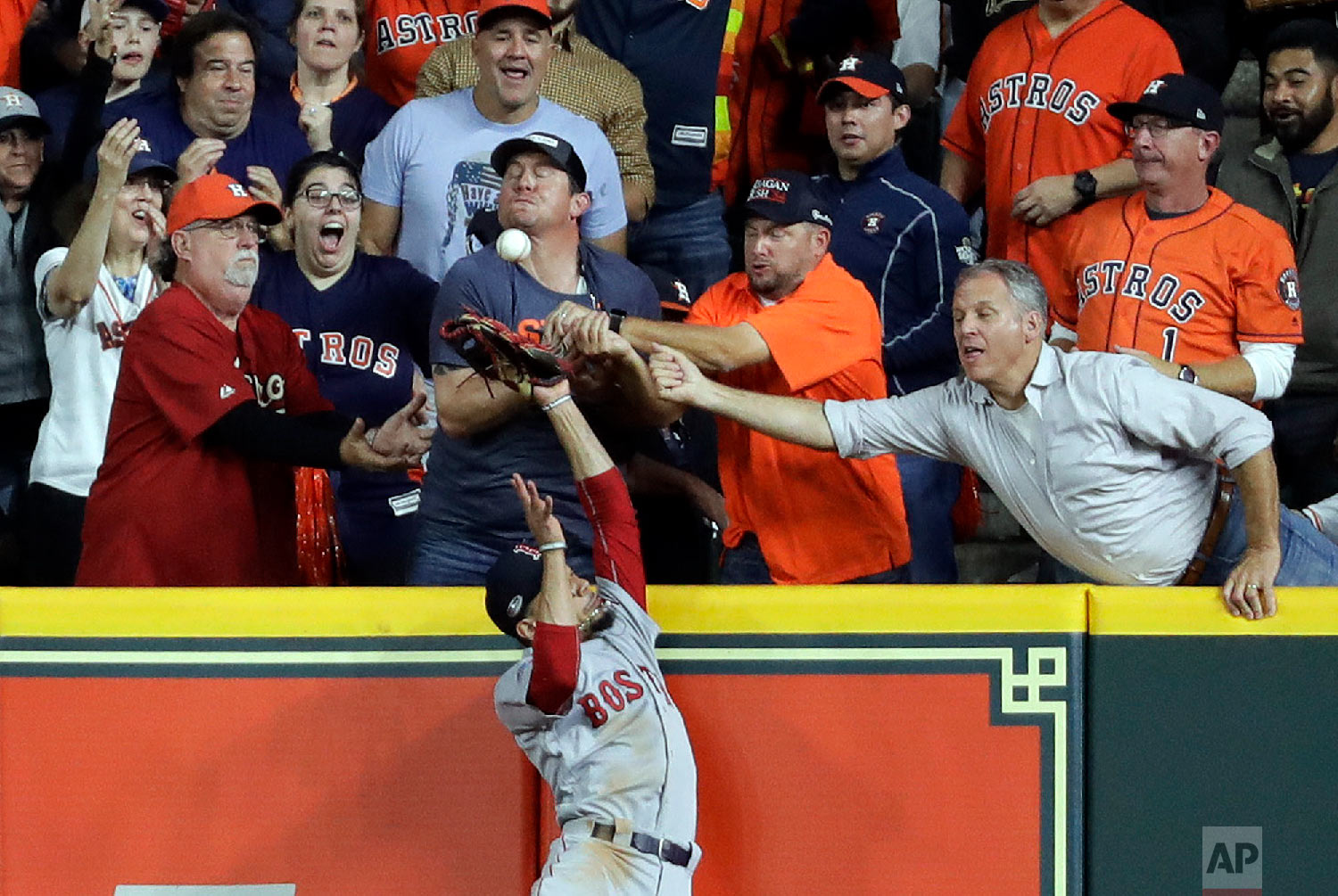 Fans interfere with Boston Red Sox right fielder Mookie Betts trying to catch a ball hit by Houston Astros' Jose Altuve during the first inning in Game 4 of a baseball American League Championship Series on Oct. 17, 2018, in Houston. Altuve was called out. (AP Photo/Frank Franklin II)
