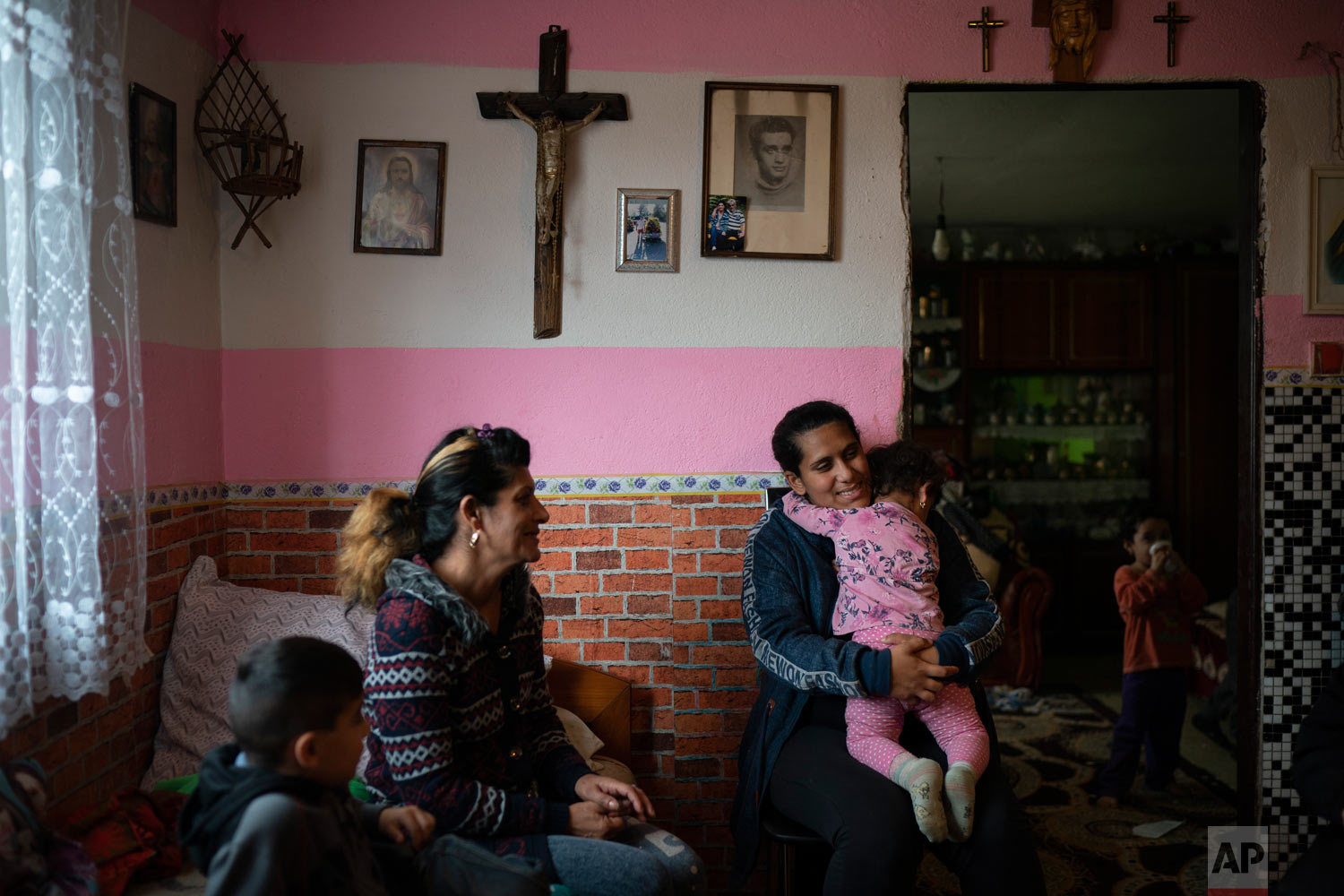 Monika Krcova, center left, sits with her daughter Ivana and her grandchildren in their house on Nov. 14, 2018, in Podhorany village, near Kezmarok, Slovakia. Krcova is no longer afraid of her local hospital since she isn't planning to have more children, but worries about her daughter Ivana, who says she also was slapped by nurses when she previously gave birth and is now pregnant. (AP Photo/Felipe Dana)