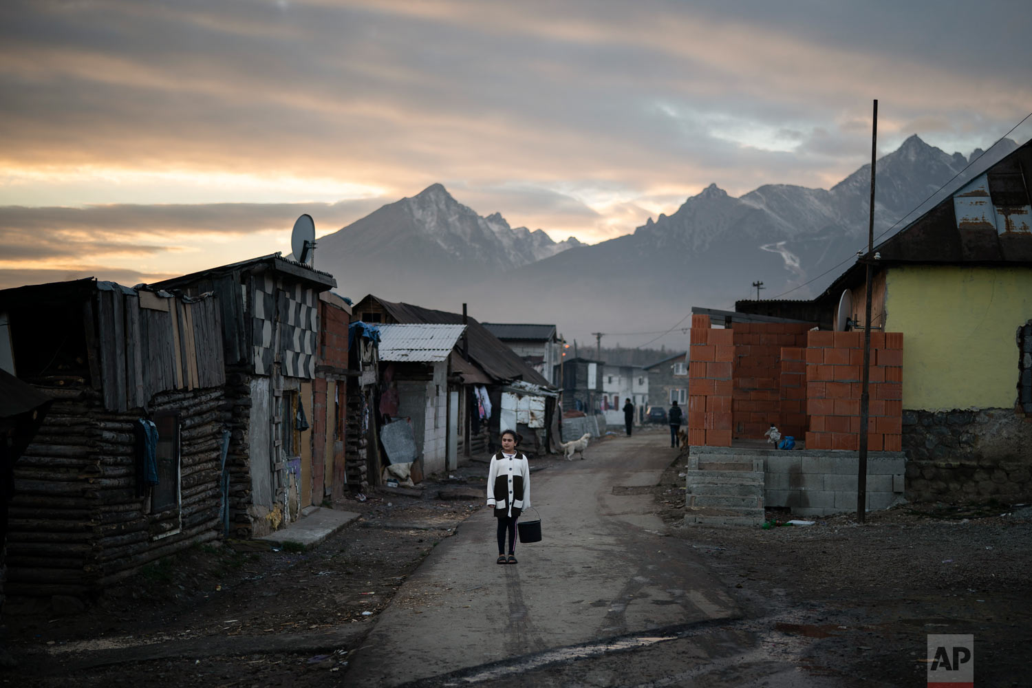 A Roma girl carries a bucket on Nov. 16, 2018, in a village near Kezmarok, Slovakia. (AP Photo/Felipe Dana)