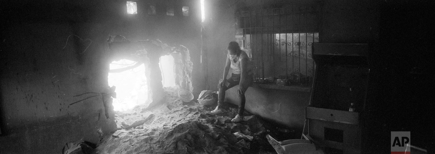 """Angelica Maria Alvarez rests, exhausted, inside her home destroyed by the eruption of the the Volcan de Fuego or """"Volcano of Fire,"""" June 14, 2018, in San Miguel Los Lotes, Guatemala. Alvarez is still searching for the remains of more than 10 family members, including her husband and two daughters. (AP Photo/Rodrigo Abd)"""